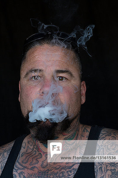 Portrait of bearded tattooed mature man looking at camera blowing smoke