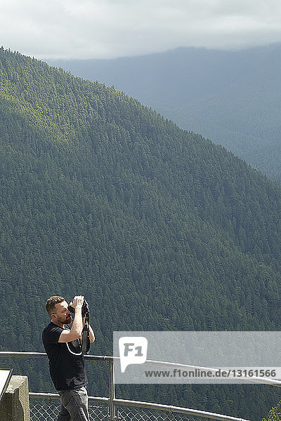 Male photographer photographing forest from viewing platform  Olympic Mountains  Washington State  USA