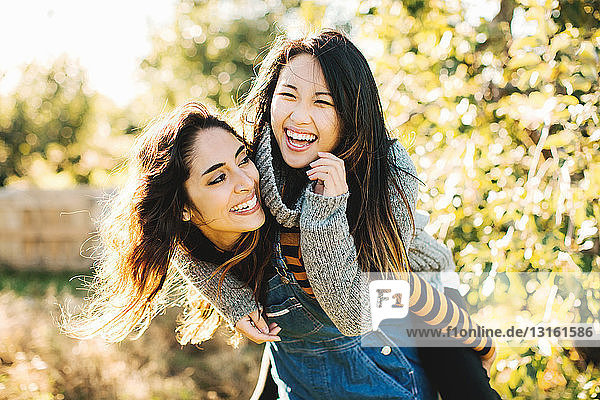 Young woman giving friend piggyback ride  outdoors