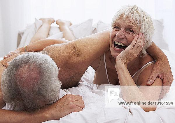 Älteres Ehepaar lacht im Bett