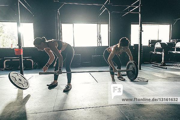 Frauen bereiten Langhantel im Fitnessstudio vor