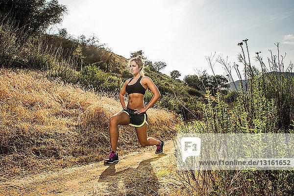 Weibliche Läuferin streckt sich in ländlicher Landschaft