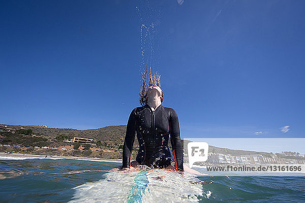 Front view of young woman on surfboard throwing back wet hair  Ventura  California  USA