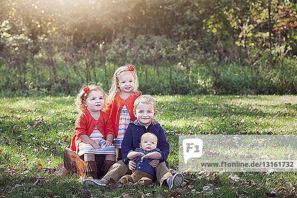 Vier Kinder einer Familie auf mit Herbstlaub bedecktem Gras posieren lächelnd für ein Foto