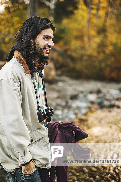 Young man  in rural environment  camera around neck  smiling