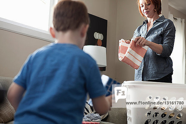 Mutter sortiert Wäsche  Sohn spielt