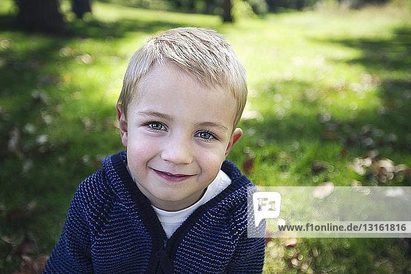 Porträt eines blonden Jungen  der lächelnd in die Kamera schaut
