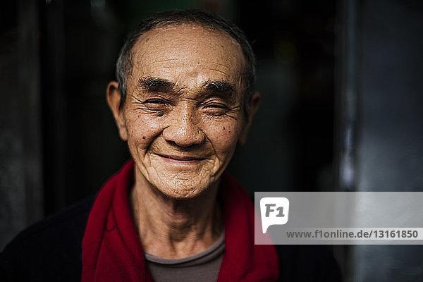Porträt eines älteren Mannes mit rotem Schal um den Hals  der lächelnd in die Kamera blickt