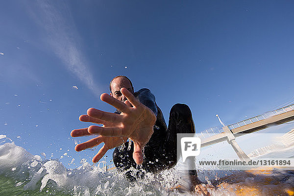 Low angled view of mid adult man surfing  looking at camera  showing hand palm  Los angeles  California  USA