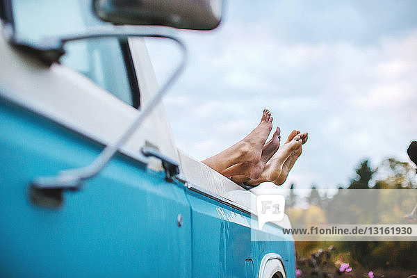 Young couple lying in back of truck  bare feet on edge of truck  focus on feet