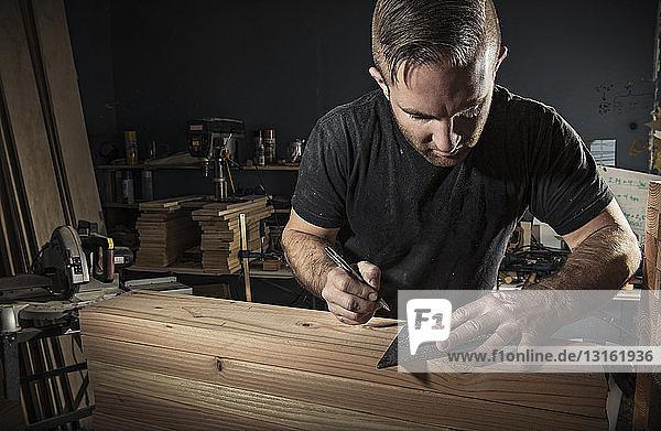 Männlicher Zimmermann misst Holzbohle mit eingesetztem Vierkant in der Werkstatt