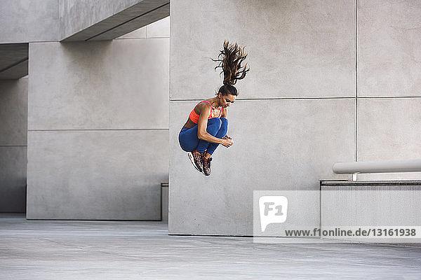 Seitenansicht einer jungen Frau  die kniehoch in die Luft springt