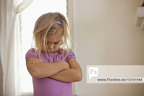 Junges Mädchen mit gesenktem Kopf und verschränkten Armen mit Wutanfall