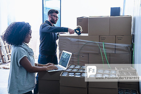Kollegen im Lager versiegeln Bierkartons mit Klebeband  organisieren die Lieferung