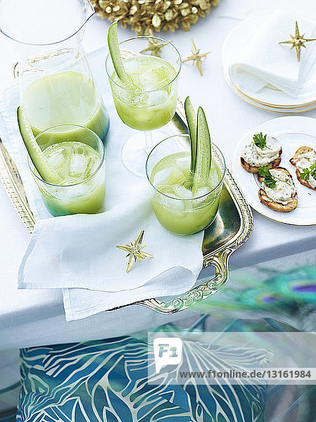 Tray of cucumber agua fresca drinks on decorated table