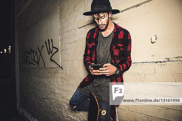 Junger männlicher Hipster lehnt nachts an der Wand und simst mit seinem Smartphone