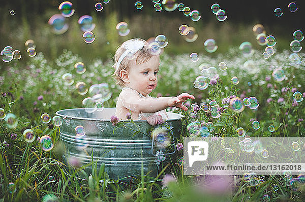 Baby girl in tin bathtub in meadow reaching for floating bubbles
