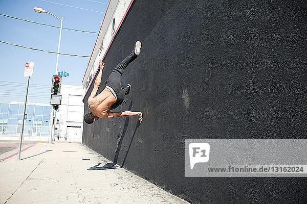 Man running up wall  demonstrating parkour