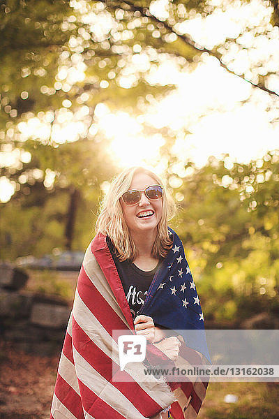Young woman wrapped in US flag  portrait