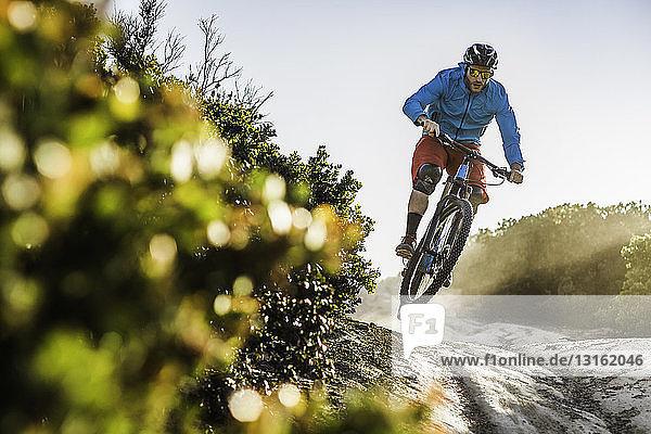 Junger Mann mit dem Mountainbike über Felsen  Monterey  Kalifornien  USA