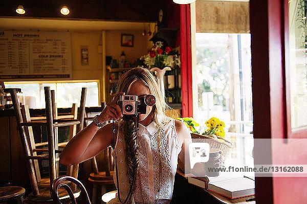 Junge Frau beim Fotografieren im Cafe