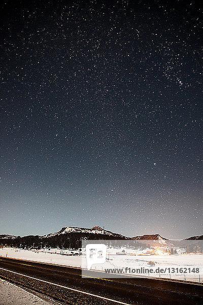 Blick auf den Highway und die schneebedeckten Berge bei Nacht  Pagosa Springs  Colorado  USA