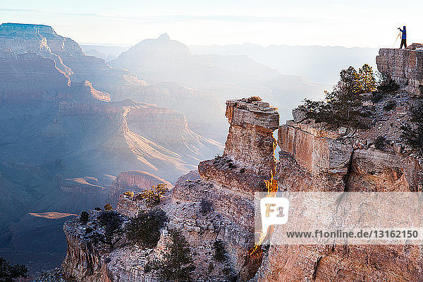 Distant silhouetted view of woman taking photographs of Grand Canyon  Arizona  USA