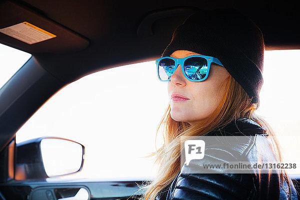 Porträt einer mittel-erwachsenen Frau auf Autofahrt mit blauer Sonnenbrille