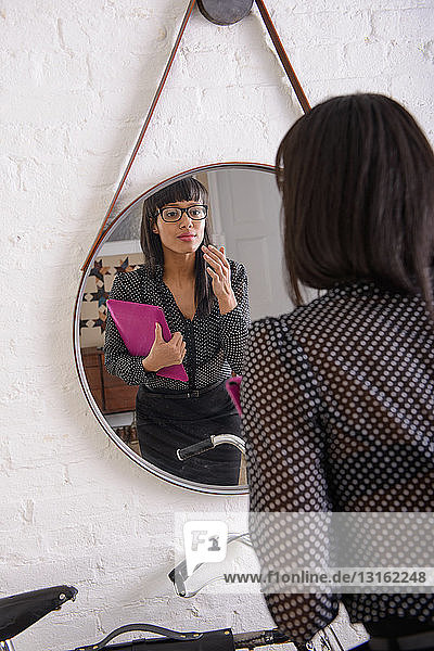 Young businesswoman looking at herself in mirror