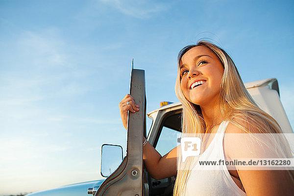 Niedrigwinkelansicht einer jungen Frau  die sich an der Tür eines Kleintransportwagens festhält