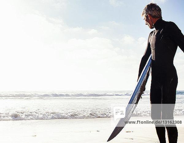 Mann an der Küste mit Surfbrett  Encinitas  Kalifornien  USA