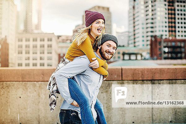 Young man giving girlfriend a piggyback on city rooftop terrace