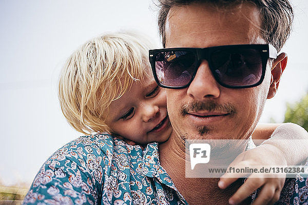 Portrait of father with son  wearing sunglasses looking at camera smiling  Luino  Lombardy  Italy