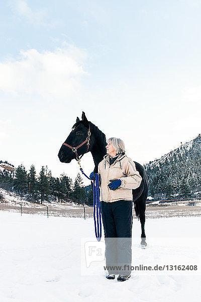 Ältere erwachsene Frau steht mit Pferd in verschneiter Landschaft