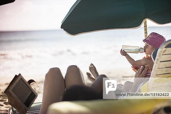 Familie liegt auf Sonnenliegen  liest und trinkt