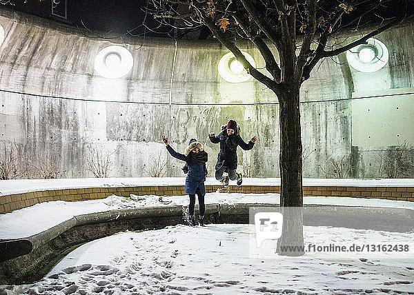Freunde springen im Schnee