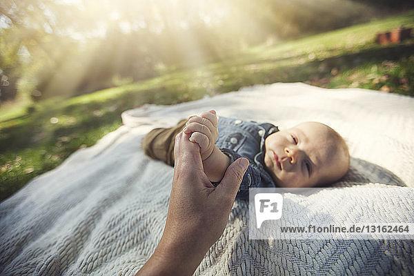 Mutter hält Hand eines kleinen Jungen  der im Sonnenlicht auf einer Decke liegt und in die Kamera schaut