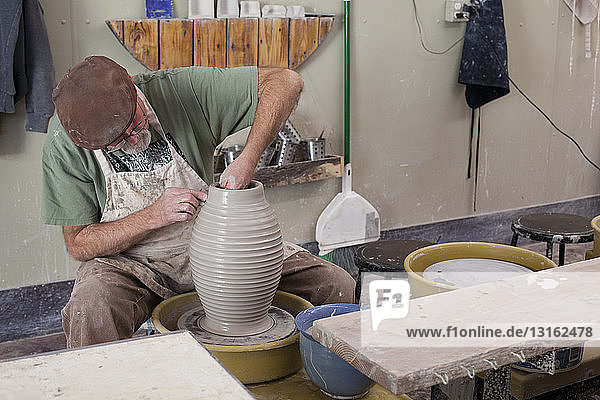 Potter wearing flat cap sitting at pottery wheel shaping clay vase