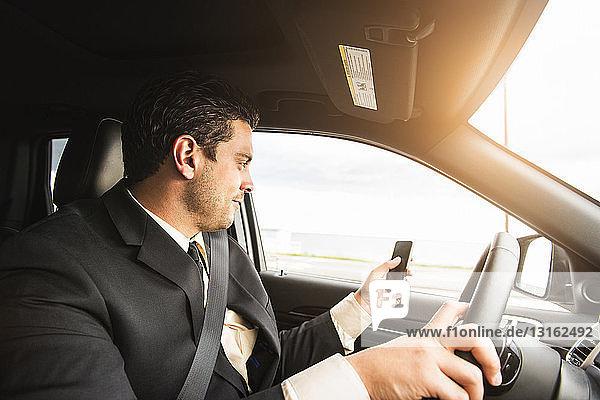 Junger Geschäftsmann fährt  während er mit einem Smartphone simst