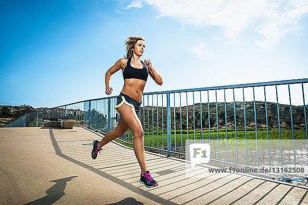 Athletische Frau läuft auf der Brücke