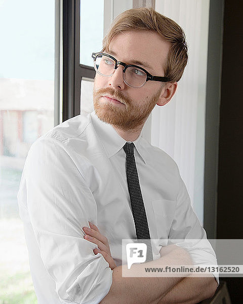 Young man wearing spectacles and tie looking away