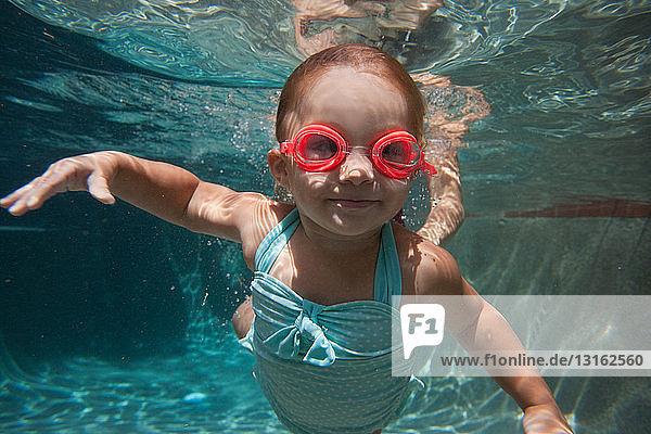 Unterwasserporträt eines Mädchens  das schwimmen lernt und vor der Kamera lächelt