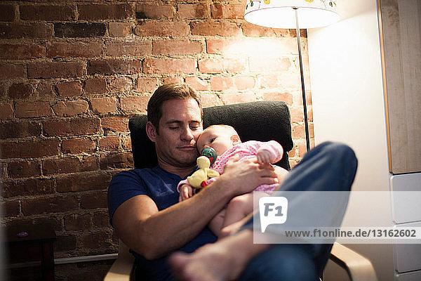 Vater hält kleine Tochter im Sessel