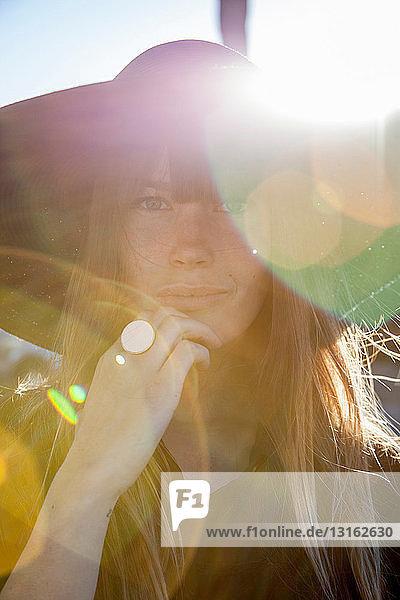 Porträt einer jungen Frau mit Hut im Sonnenlicht