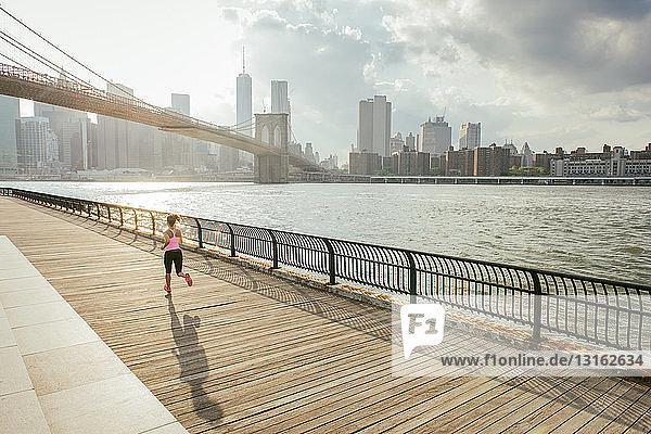 Junge Läuferin läuft am Flussufer  Brooklyn  New York  USA