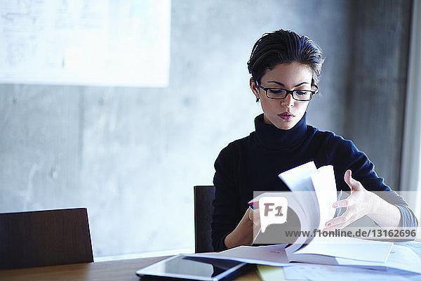 Junge Geschäftsfrauen durchsuchen Arbeitsheft im Büro