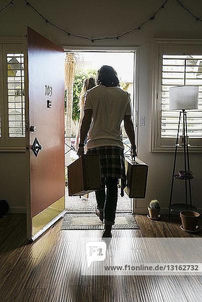 Rückansicht eines jungen Paares  das Koffer aus der Haustür trägt