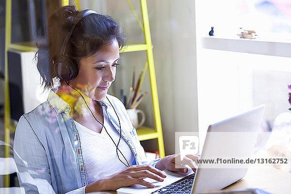 Junge Frau mit Kopfhörern am Laptop