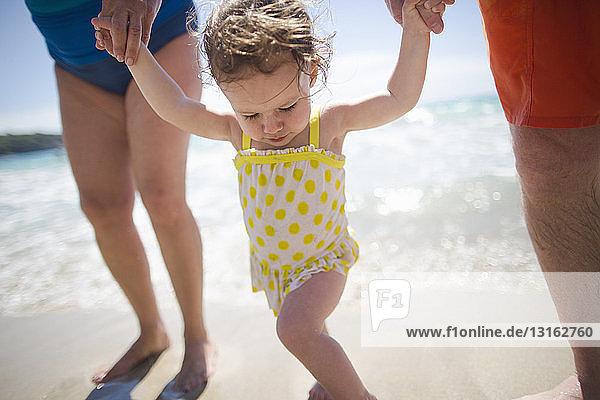 Kleinkind und Großeltern halten Händchen und gehen am Strand spazieren