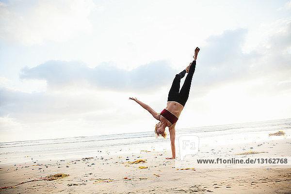 Mittlere erwachsene Frau  die Yogastellung am Strand praktiziert